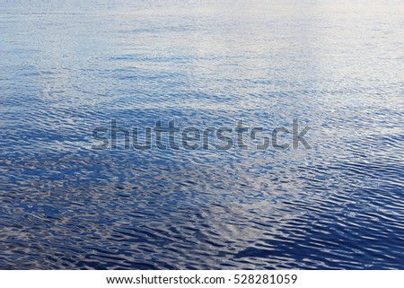 cloudless blue sky reflected in the smooth surface of the Northern Dvina River. blue background.