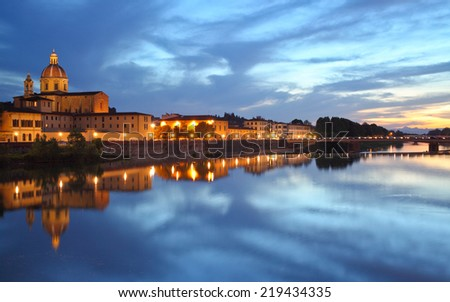 Clouds above Arno River at night, Florence, Italy. Cityscape with reflection.
