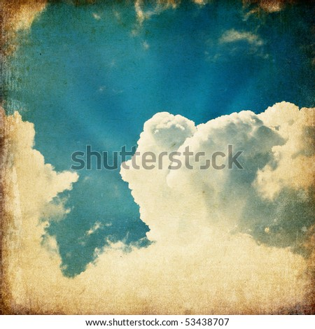 Clouds and a blue sky with a sun-rays shining through, useful as background element in design-works. - stock photo