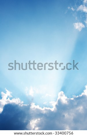 Clouds and a blue sky with a sunbeam shining through - stock photo