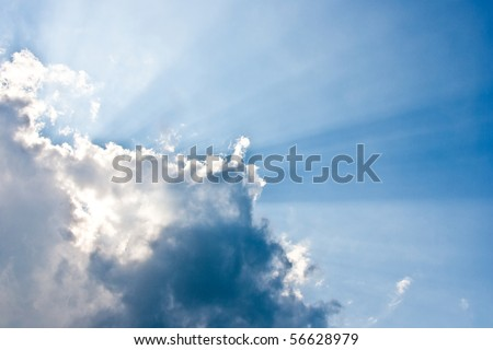 Clouds and a blue sky with a sunbeam shining through.