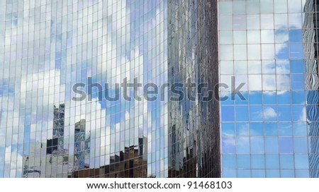 Clouds and buildings reflecting on a skyscraper glass facade - stock photo