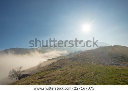 Clouds and fog gathering on the mountain ridge in a sunny afternoon. Wide angle shot in backlight in the italian western Alps. - stock photo