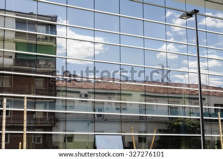 clouds and house  reflected in windows of a building of company  