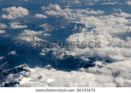 Clouds and mountains taken from above from an air craft - stock photo