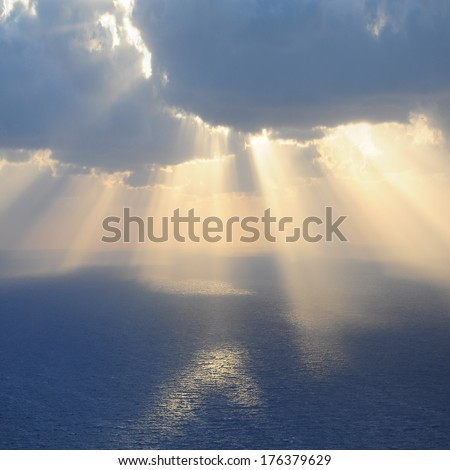Clouds and rays of sun above the sea. - stock photo