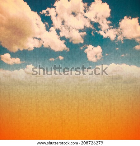 Clouds and sand on a textured vintage paper background with grunge effect applied  - stock photo
