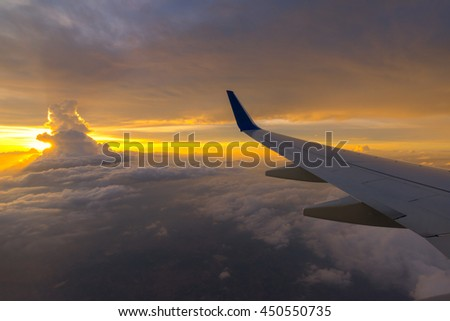 Clouds and sky as seen through window of an aircraft. Looking through window aircraft during flight in wing with a nice blue/purple/orange sky.