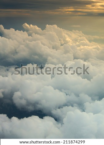 Clouds and sky with dramatic heaven light as seen through window of an aircraft - stock photo