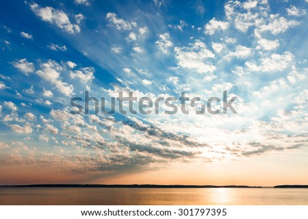 Clouds and sun rays over lake at sunrise - stock photo