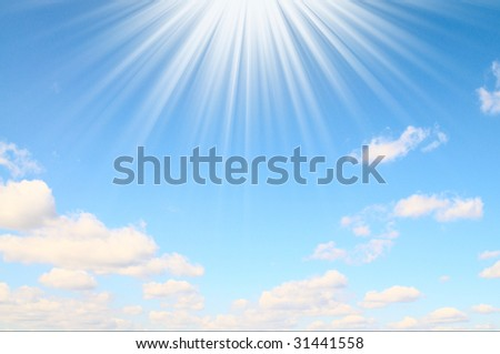 Clouds and sunbeams on a blue sky.