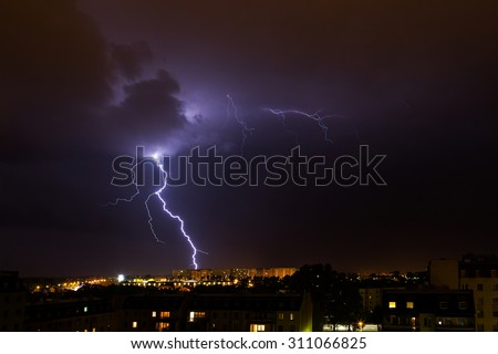 Clouds and thunder lightnings and storm over city.