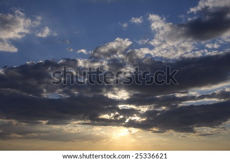 Clouds bathing in solar beams in the blue sky