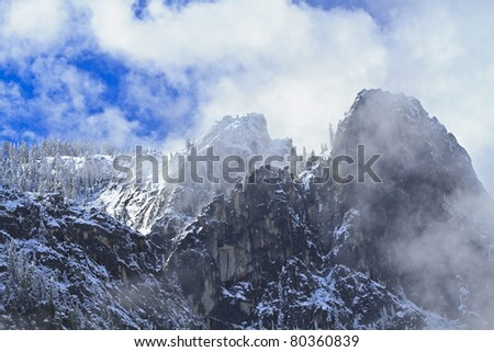 Clouds clearing on Cathedral Rocks with a fresh coating on snow on the ridge trees in Yosemite National Park, California - stock photo