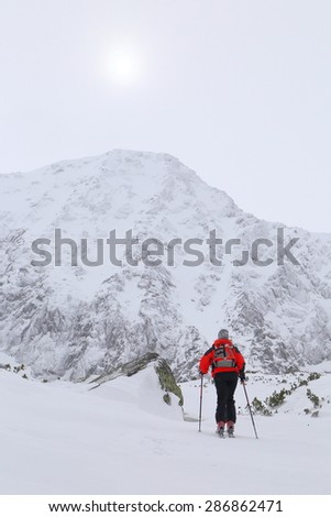 Clouds cover the sun above the mountain and woman climbing on touring skis - stock photo