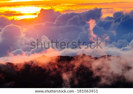 Clouds covering distant mountains at sunrise over Haleakala Crate on Maui, Hawaii, USA - stock photo