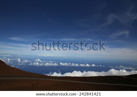 Clouds, distant ocean and mountains viewed from Haleakala peak - stock photo