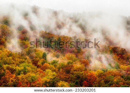 Clouds floating among the mountains covered in fall colored trees. - stock photo