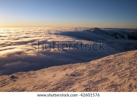 Clouds flowing over a mountain range - stock photo