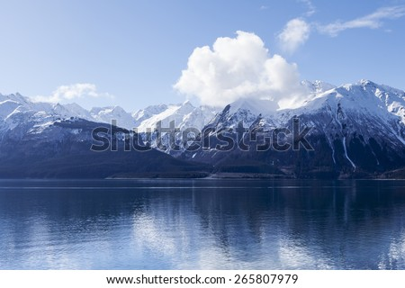 Clouds forming over the Chilkat mountains reflected in the water of the inlet near Haines Alaska. - stock photo