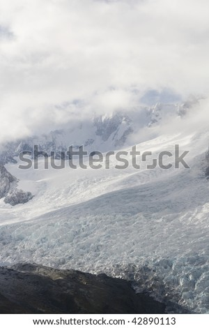 Clouds hanging above the top of Franz Joseph Glacier in New Zealand - stock photo
