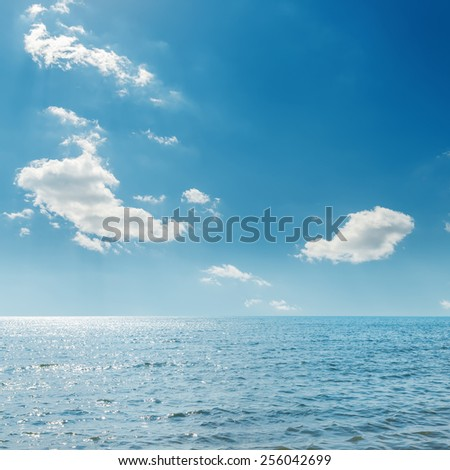 clouds in blue sky over sea - stock photo