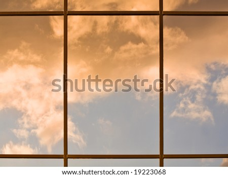 Clouds lit by the setting sun reflecting in a modern office building windows - stock photo