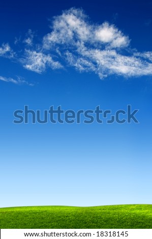 clouds on blue sky above green meadow - stock photo