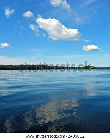 Clouds over a blue lake - stock photo