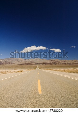 clouds over a very straight road in Death Valley - stock photo