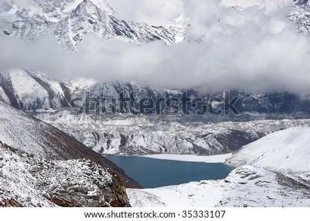 Clouds over glacier and mountain lake, Himalaya - stock photo