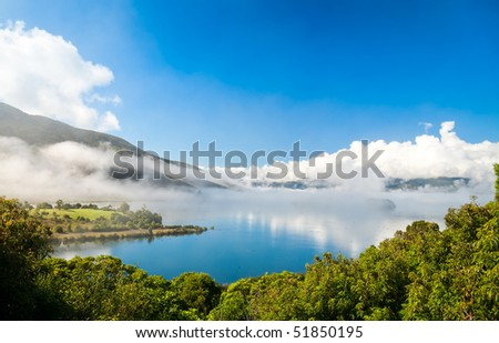Clouds over Lake Rotoaria, New Zealand. Dots on water surface are swans - stock photo