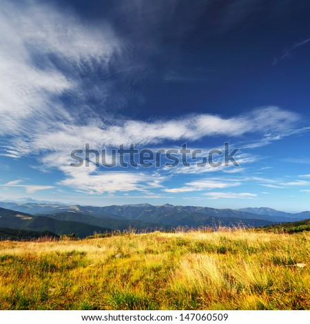 clouds over mountains and yellow grass on foreground, square panorama in summer day - stock photo