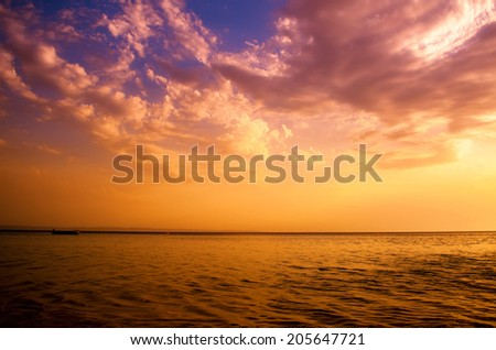Clouds over sea at sunset - stock photo
