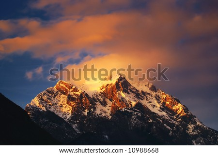 Clouds over the mountain peak at dusk - stock photo