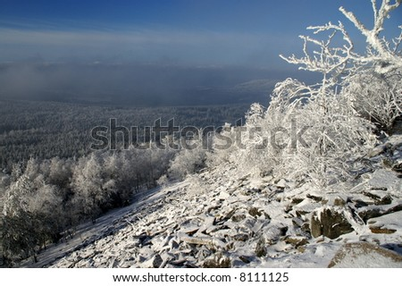 Clouds over the snow covered valley with stone field in foreground. - stock photo