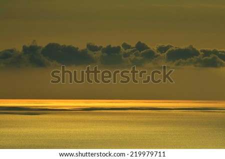 Clouds passing low over the sea at sunset - stock photo