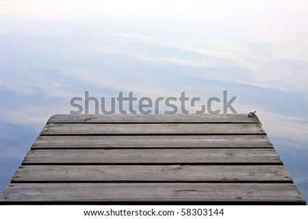 Clouds reflected in the lake at the end of a wooden pier - stock photo