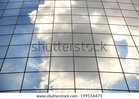 Clouds reflected in wall of modern office building. - stock photo