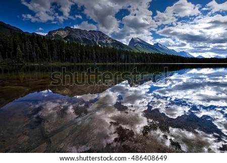 Clouds reflection in calm water. Honeymoon lake in Canadian Rockies. Jasper National Park. Alberta. Canada.