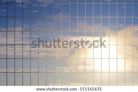 clouds reflection in glass wall of skyscraper - stock photo