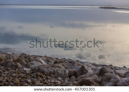 Clouds reflection in water of Dead Sea at stony beach with man on headland and misty horizon - stock photo