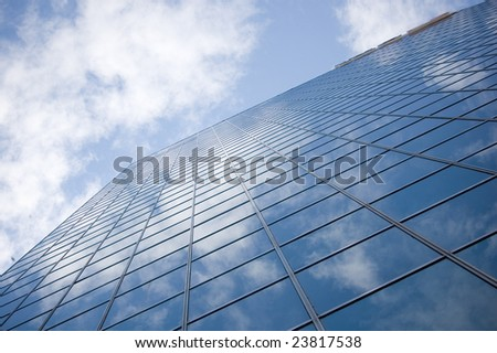 clouds reflection on highrise glass building against sky