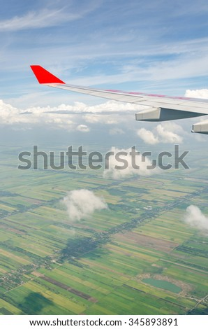 Clouds, sky and field as seen through window of an aircraft - stock photo