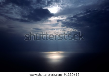 clouds with god rays on a beautiful seascape - stock photo