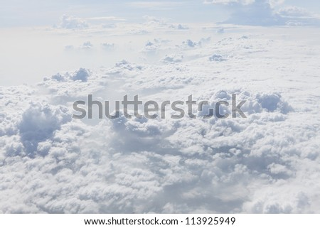Cloudscape and stratosphere shot out of an airplane window./above the clouds - stock photo