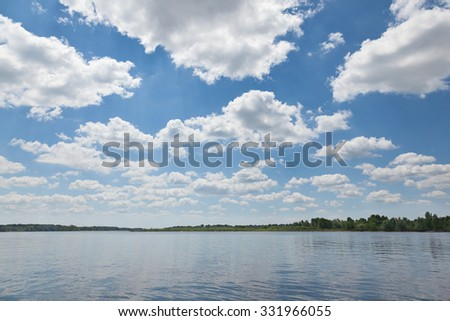 Cloudscape at sunny summer day over calm lake