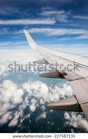 Cloudscape. Blue sky and white cloud. Sunny day. Wing of aircraft.