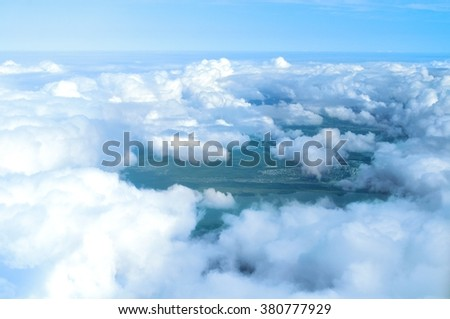 Cloudscape in sunny weather - white dense clouds floating over land surface, birds eye view  - stock photo