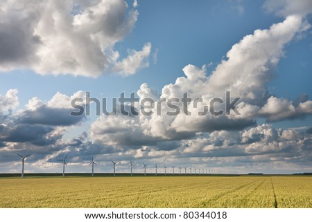 Cloudscape in the evening sunlight above Dutch crop fields - stock photo